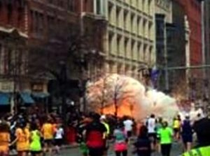 In this image from video provided by WBZ-TV, spectators and participants scramble away from what authorities described as two explosions at the finish line of the Boston Marathon.