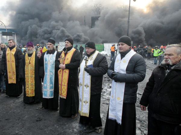 Priests of different faiths pray during clashes with police in central Kiev, Ukraine, Thursday, Jan. 23, 2014. Thick black smoke from burning tires engulfed parts of downtown Kiev as an ultimatum issued by the opposition to the president to call early elections or face street rage was set to expire with no sign of a compromise on Thursday. (AP Photo/Sergei Chuzavkov)
