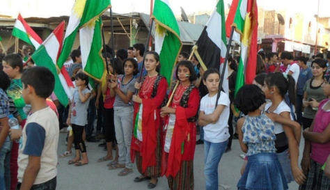 Demonstrators hold Kurdish and Syrian opposition flags during a protest in Kobani