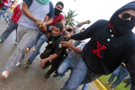 Demonstrators apprehend a riot police officer near the airport in Acapulco(AFP)