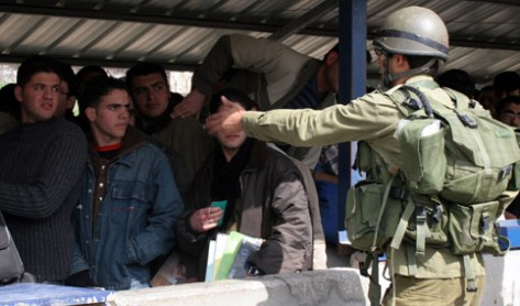 An Israeli soldier prevents Palestinians from passing Beit Iba checkpoint, during a demonstration against Israeli checkpoints near the West Bank city of Nablus, 14 February 2007. (MaanImages/Rami Swidan)