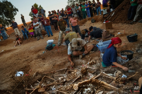 In this photo taken on July 26, 2014, volunteer archaeologists, anthropologists and forensic scientists from the Aranzadi Sciences Society and Association for the Recovery of Historical Memory of Burgos work in what it was a hidden mass grave in El Estepar, Spain. (AP Photo/Daniel Ochoa de Olza)
