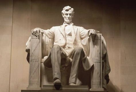 the statue of abraham lincoln in washington, d.c. shows him resting his arms on two fasci.